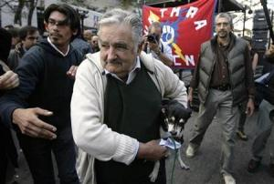Uruguayan President Jose Mujica arrives for the celebration of the Worker's Day carrying his pet dog Manuela